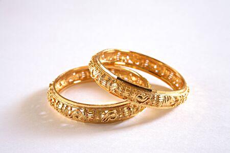 概念、白い背景の手首で身に着けている kangan の金のバングル 写真素材