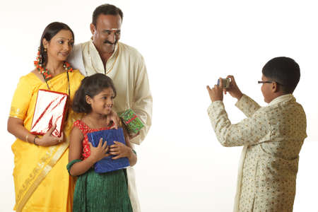 South Indian son photographing parents and sister in mobile phone Stock Photo