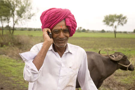 Cowman talking on mobile phone in Salunkwadi,Ambajogai,Maharashtra,India