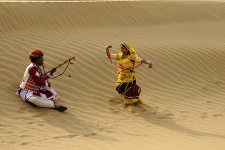 Couple playing folk music and dancing in sand dunes,Jaisalmer,Rajasthan,India