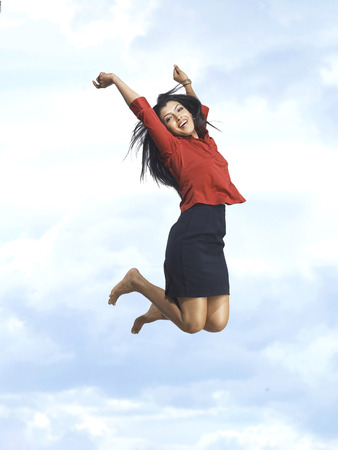Executive jumping with joy in blue sky Stock Photo