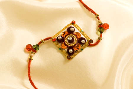 Concept,rakhi tie of guarding silk string on silk cloth for Rakshabandhan festival Stock Photo