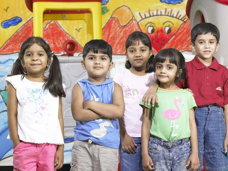 南アジアのインディアンの少年と少女が保育園で一緒に立っている