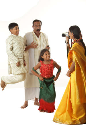 South Indian mother photographing father and children in video camera