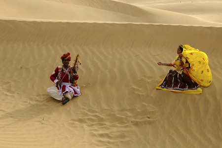 Couple playing folk music and dancer in sand dunes,Jaisalmer,Rajasthan,India