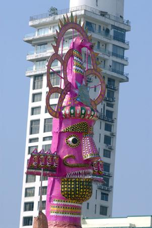 Demon king of Lanka Ravana skyscraper behind made for dahan celebrating Dussera festival at Chowpaty,Charni Road,Bombay Mumbai,Maharashtra,India