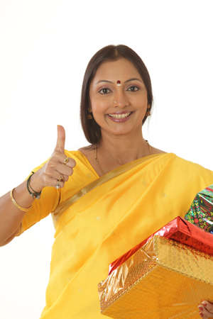 goodluck: South Indian lady holding gifts in hand showing thumb gesture LANG_EVOIMAGES