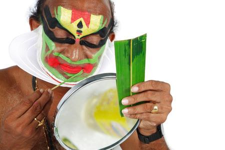 South Indian kathakali dancer applying makeup looking in mirror,Kerala,India
