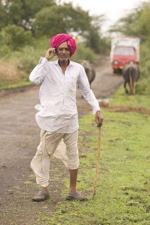 Cowman holding stick in hand talking on mobile phone in Salunkwadi,Ambajogai,Maharashtra,India