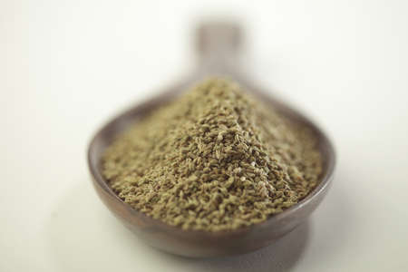 Spices,bishop weed ajowan ajwain trachysrermum ammi carum ajowan carum copticum  in wooden ladle on white background