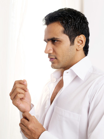 Man buttoning cuff of shirt Stok Fotoğraf