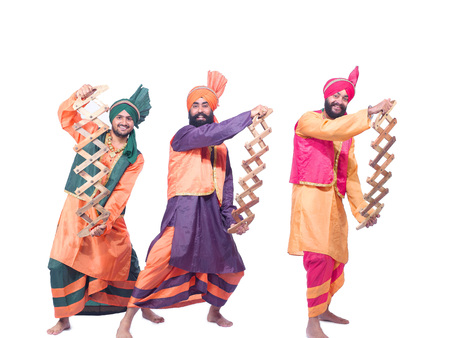 Dancers playing musical instrument performing folk dance bhangra