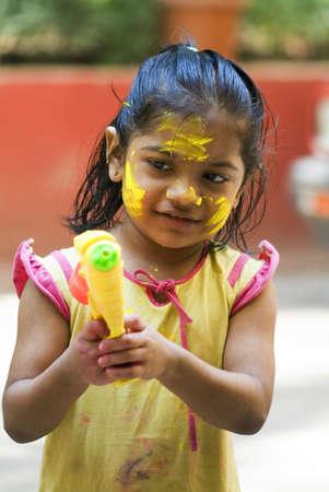 Seven year old girl playing syringe during holi festival,Bombay Mumbai,Maharashtra,India Stock Photo
