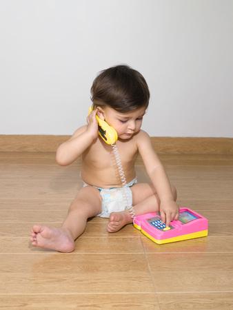 電話セットで遊んでおむつを着て、赤ちゃん