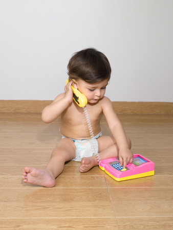 Tragende Windel des Babys, die mit Telefonapparat spielt Standard-Bild - 85909461