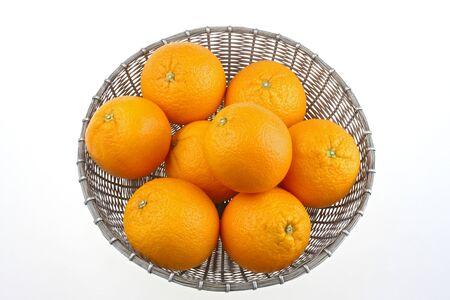 Eight oranges in a metal basket citrus reticulata clementin rutaceae,India Stock Photo