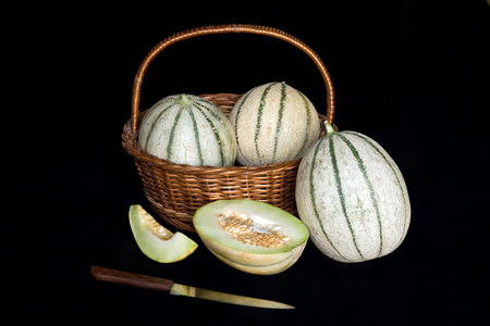 Three full and one cut charentais melon with cane basket,India