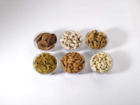 Dryfruit and nut,almonds raisins cashewnuts figs pistachios walnuts in bowls on white background Reklamní fotografie