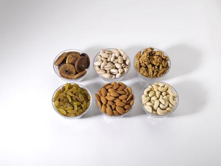 Dryfruit and nut,almonds raisins cashewnuts figs pistachios walnuts in bowls on white background Foto de archivo
