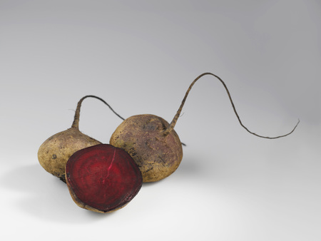 Two full and half beetroot on white background