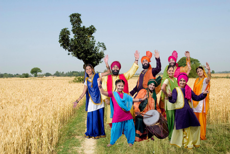 Sikh family with dancers performing folk dance bhangra in wheat field