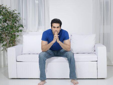 ソファーに座っていた男性 写真素材
