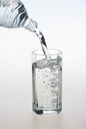 Pouring water in transparent crystal glass,India