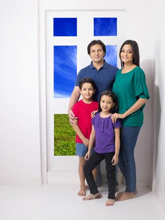 Parent with children standing on doorway Foto de archivo