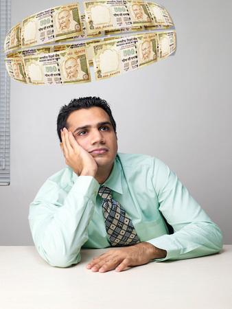 Executive thinking surrounded by flying money