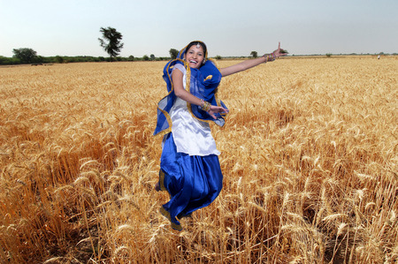 Dancer performing folk dance bhangra in wheat field