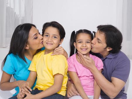 Parent kissing their children