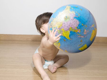 Baby wearing diaper playing with a globe
