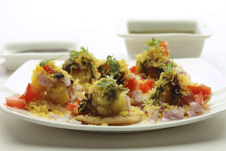 sev: Fast food,chat chaat sev puri toppings of chutney tomato onion and sev in plate on white background