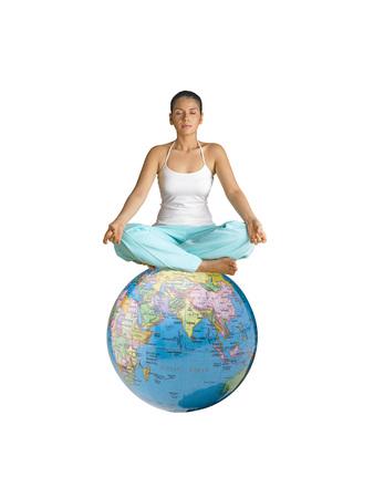Lady doing yoga sitting on globe Stock Photo