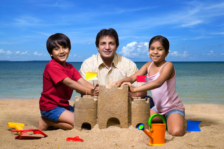 Father with children at sandcastle on seashore