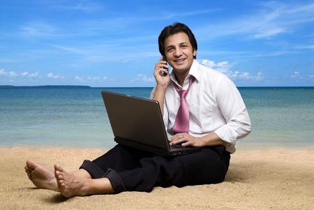 海岸で砂の上に座ってノート パソコンと携帯電話で話して執行
