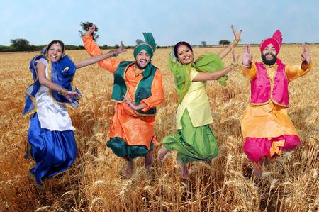 Dancers performing folk dance bhangra in wheat field