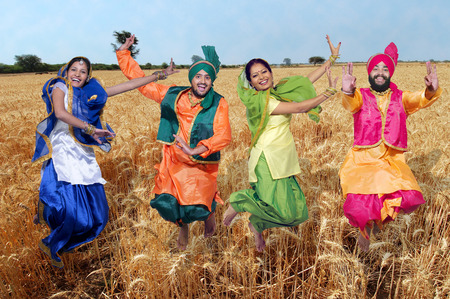 Dancers performing folk dance bhangra in wheat field