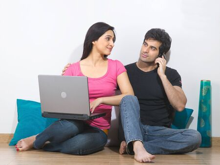 Man talking on phone and women with laptop