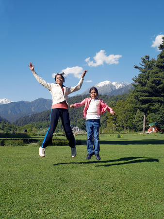Girls jumping with joy in indira gandhi park,Pahalgam,Jammu and Kashmir,India Foto de archivo