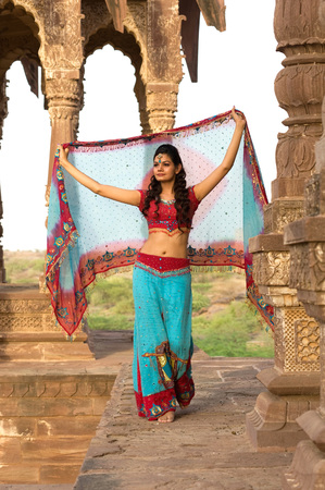 Lady in traditional wearing holding dupatta walking at heritage structure,India
