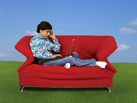 Man working on laptop talking on mobile phone sitting on red sofa on green grass