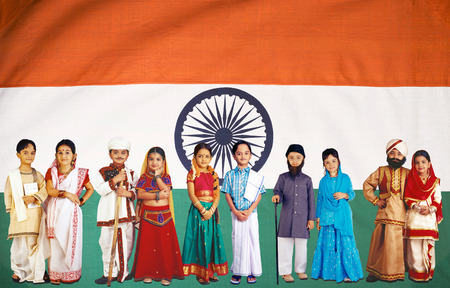 Children in fancy dress national flag behind them Stock Photo