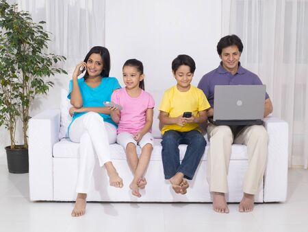 contemporary living room: Woman and son using mobile while man using laptop and daughter with remote