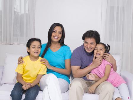 소파에 앉아있는 아이들과 부모