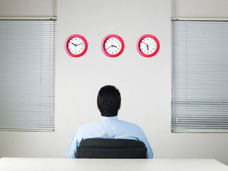 Executive looking at row of clocks