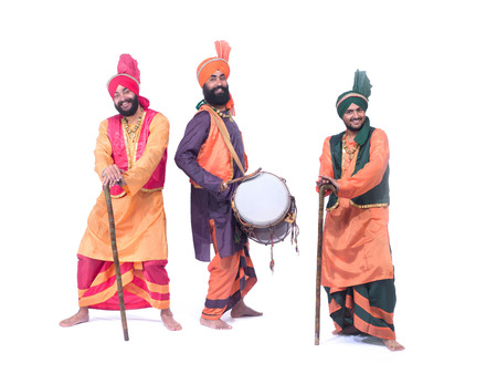 Dancers playing musical instrument dholak performing folk dance bhangra