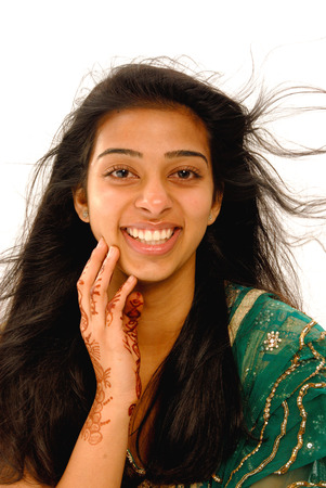 Chica joven que ríe volando su pelo en el fondo blanco