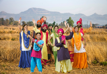Sikh family with dancers performing folk dance bhangra in dry grass