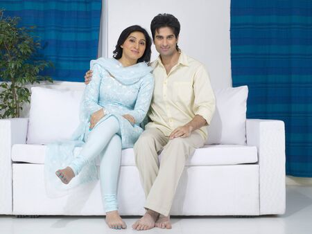 Couple sitting on sofa Stock Photo